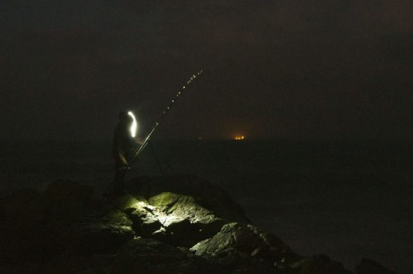 Pre-dawn fishing from the Aberdeen coastline with the lights of oil service boats in the background