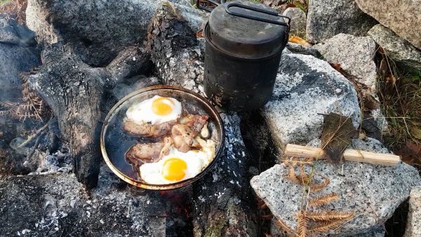 Bacon and eggs on the campfire. And a fish biting...