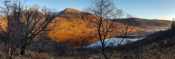 Golden light floods over Ben Starav as the sun starts to set over a mirror like Loch Etive, just after Christmas.