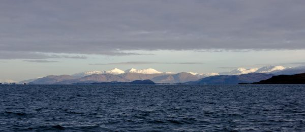 Cold, grey sea with a background of the Nevis range of mountains covered in snow