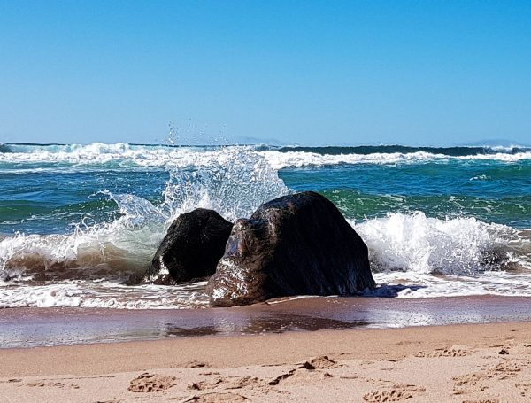A wave breaks against a boulder embedded in the sand
