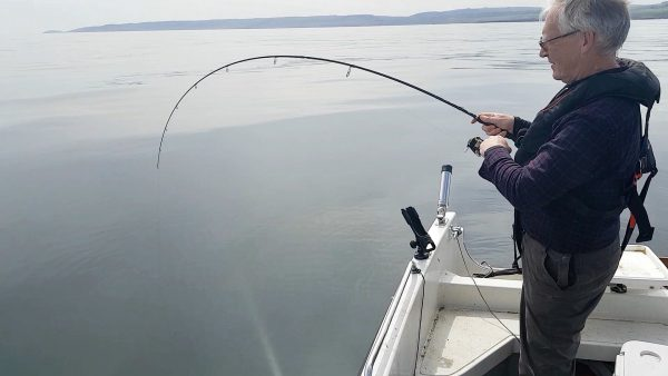 With my rod hooped over as he dives, this pollack makes it clear it doesn't want to come aboard my boat