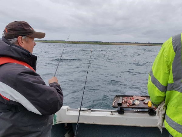 Ian and Trevor fishing for codling from Ian Raider boat on an overcast and windy day at St Andrews.