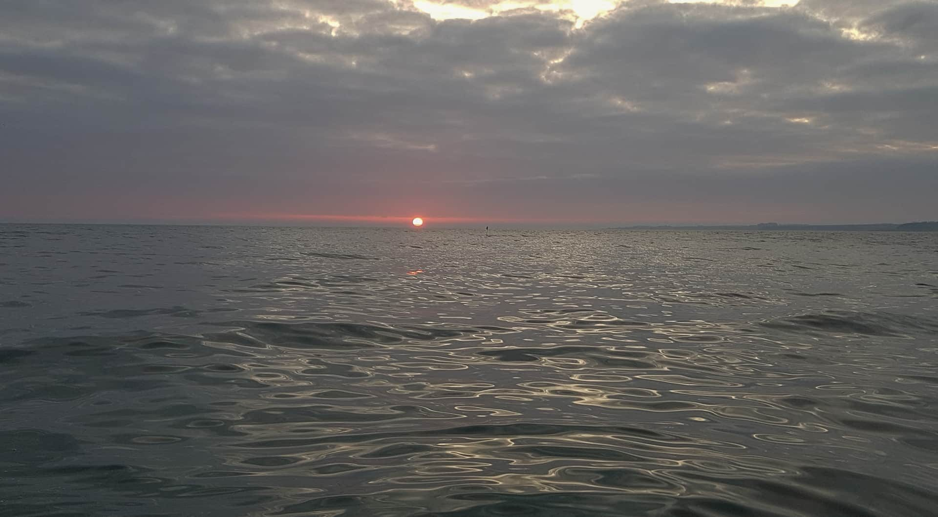 The sun rises over a placid North Sea as we leave St Andrews harbour in mid-November
