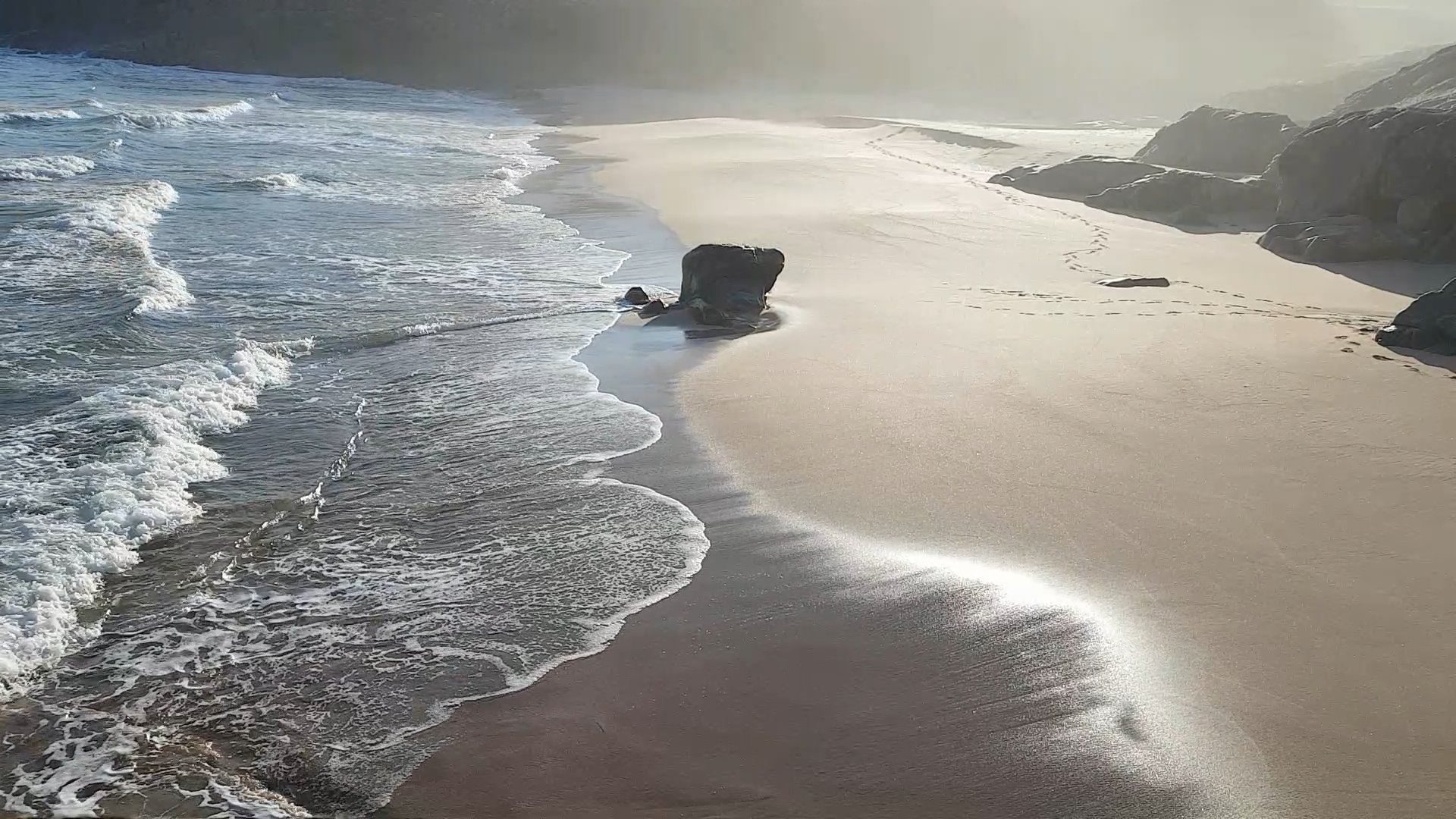 Early morning sun and mist light up the sand as a small surf hits the beach near Sandwood, Scotland