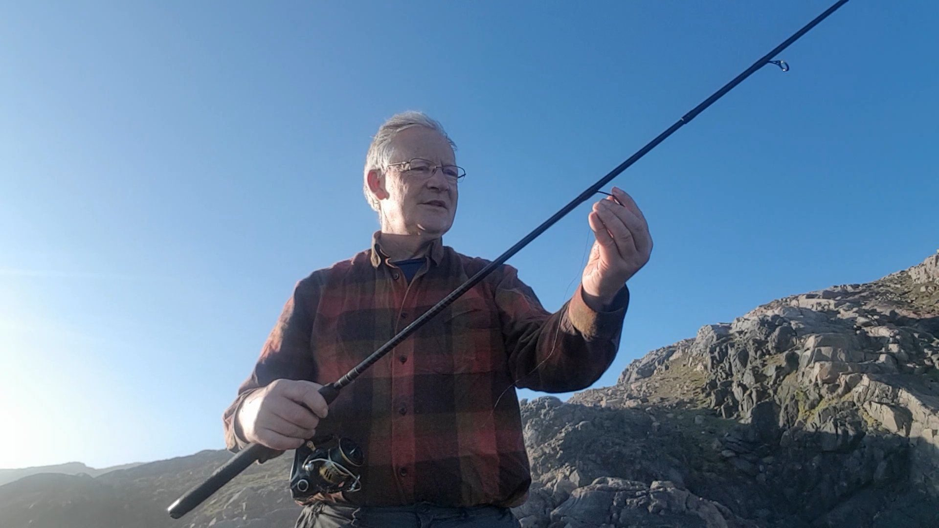 Tackling up for a light sea fishing session with a spinning rod, a few miles south of Cape Wrath, Scotland