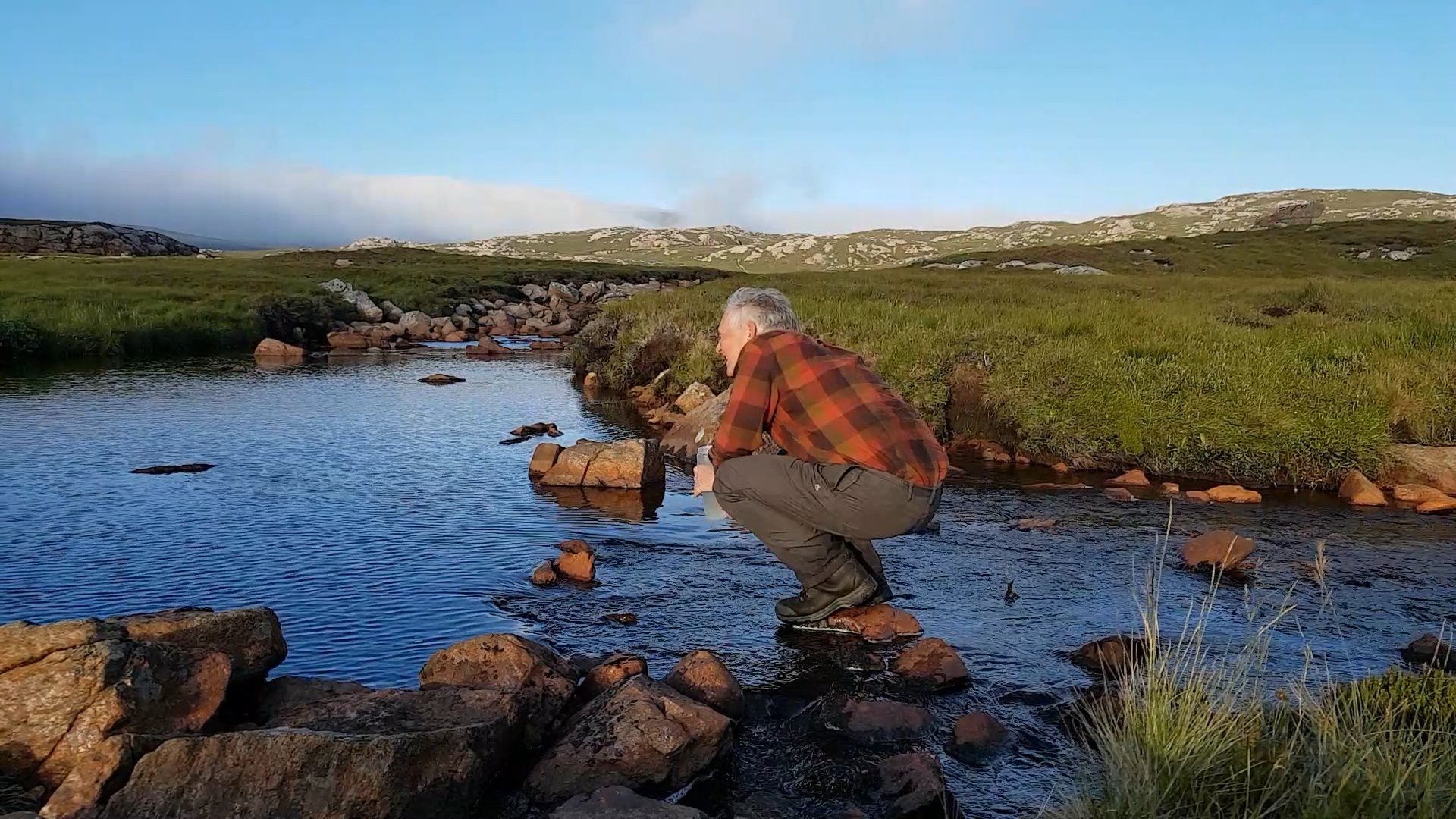 Collecting fresh water from the peaty burn at Strath Chailleach, near Cape Wrath, NW Scotland